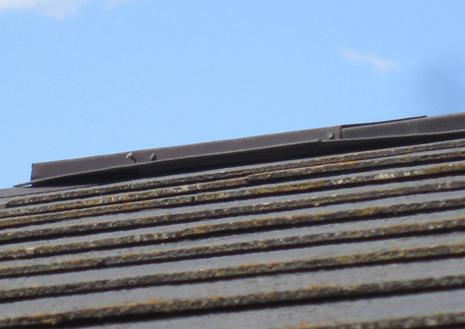 棟(屋根最上部の被せ板金)が反っています。釘も飛び出しています。雨漏りの原因です。